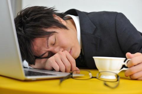 仕事中居眠りをする男性