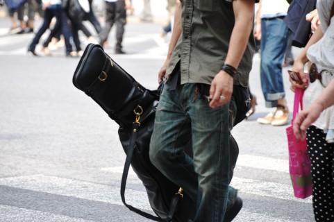 ギターを持って歩く青年