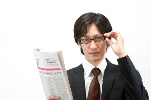 新聞を持った男性